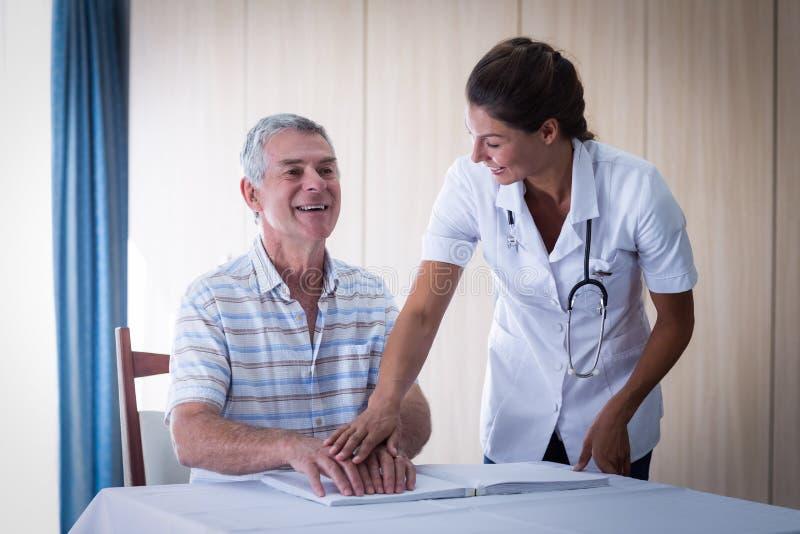 Θηλυκός γιατρός που βοηθά τον ασθενή στην ανάγνωση του βιβλίου μπράιγ στοκ εικόνες