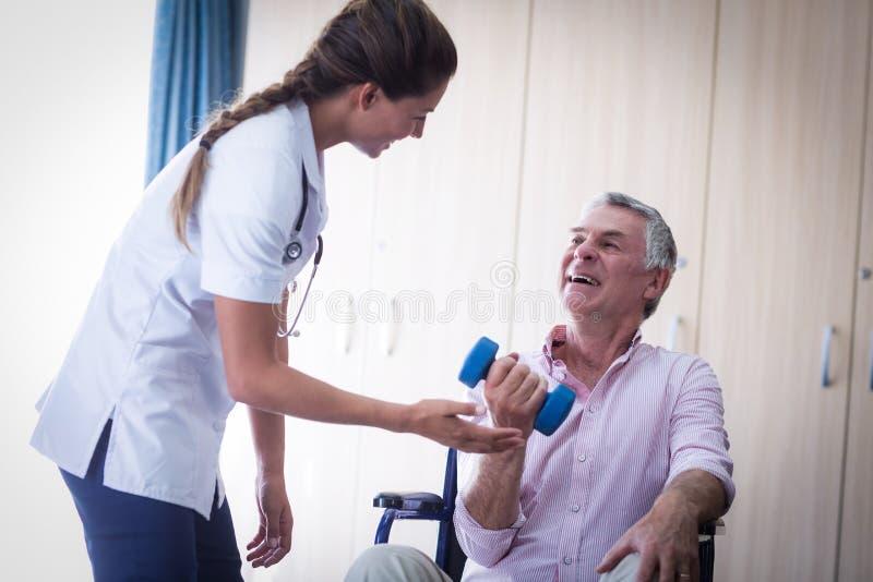 Θηλυκός γιατρός που βοηθά το ανώτερο άτομο στην ανύψωση του αλτήρα στοκ εικόνες
