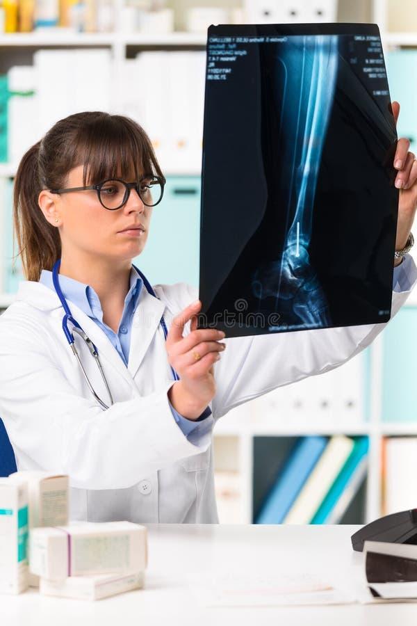 Θηλυκός γιατρός που εξετάζει την ακτίνα X ασθενών στοκ εικόνες