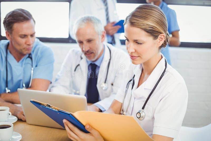 Θηλυκός γιατρός που εξετάζει την ιατρική έκθεση στοκ φωτογραφίες με δικαίωμα ελεύθερης χρήσης