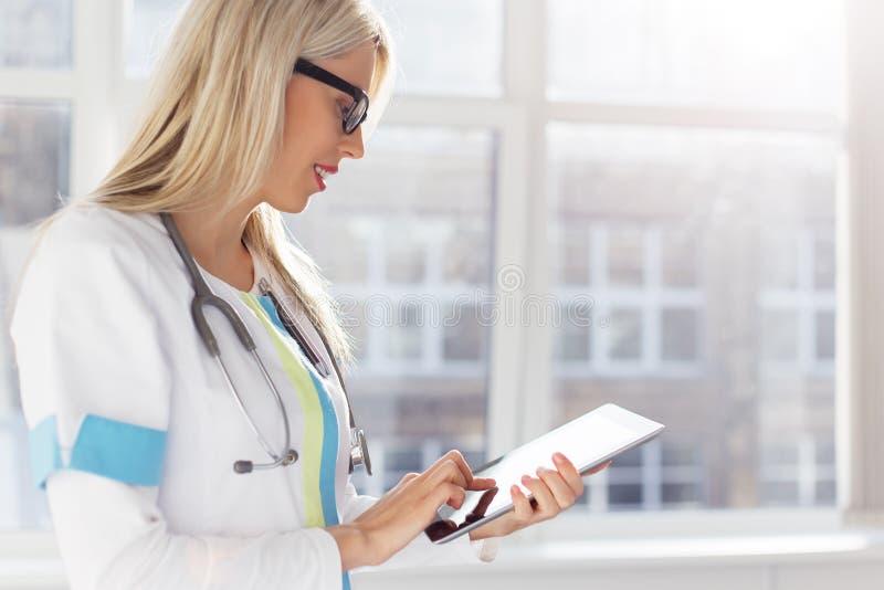 Θηλυκός γιατρός που κοιτάζει στον υπολογιστή ταμπλετών στοκ εικόνα