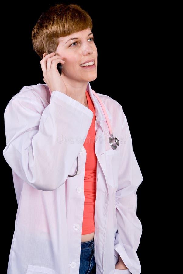 Θηλυκός γιατρός που μιλά σε ένα τηλέφωνο κυττάρων στοκ εικόνες