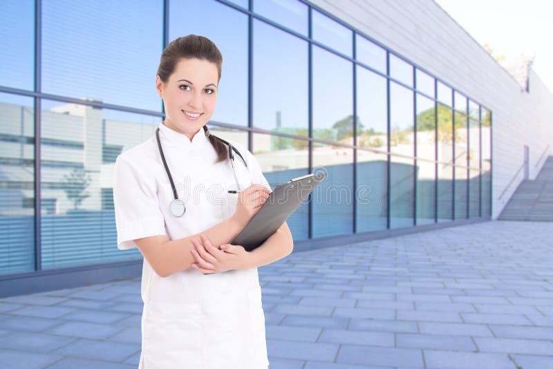 Θηλυκός γιατρός που στέκεται ενάντια στο σύγχρονο κτήριο νοσοκομείων στοκ φωτογραφία