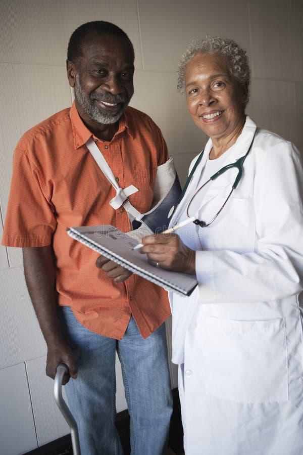Θηλυκός γιατρός που στέκεται με το με ειδικές ανάγκες ασθενή στοκ φωτογραφίες