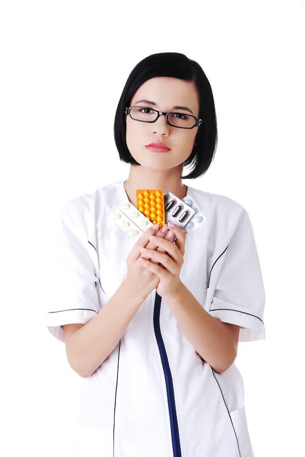 Θηλυκός γιατρός στα ομοιόμορφα χάπια εκμετάλλευσης στοκ φωτογραφία με δικαίωμα ελεύθερης χρήσης