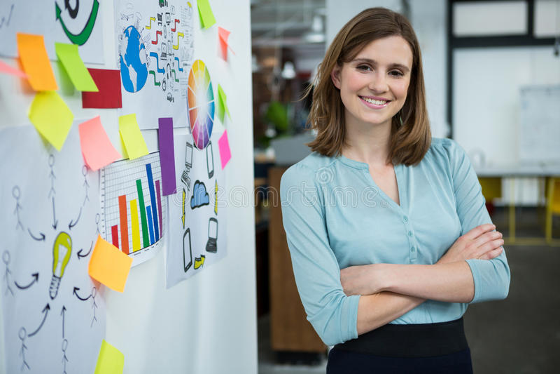 Θηλυκός γραφικός σχεδιαστής που στέκεται με τα χέρια που διασχίζονται στο δημιουργικό γραφείο στοκ φωτογραφία με δικαίωμα ελεύθερης χρήσης