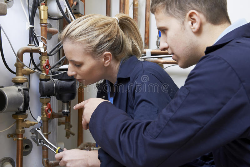 Θηλυκός εκπαιδευόμενος υδραυλικός που εργάζεται στο λέβητα κεντρικής θέρμανσης στοκ εικόνα