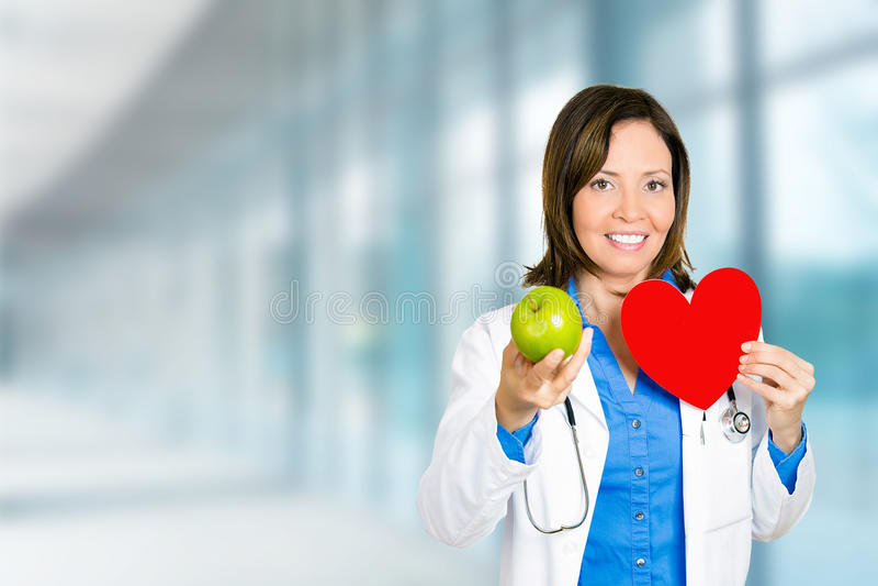 Θηλυκός επαγγελματίας υγειονομικής περίθαλψης γιατρών με το κόκκινο πράσινο μήλο καρδιών στοκ φωτογραφία με δικαίωμα ελεύθερης χρήσης