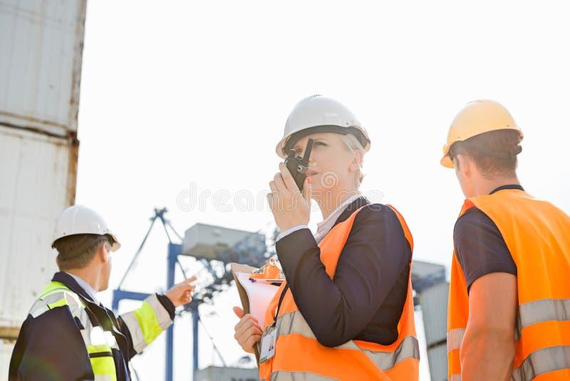 Θηλυκός επόπτης που χρησιμοποιεί walkie-talkie ενώ εργαζόμενοι που συζητούν στο υπόβαθρο στο ναυπηγείο στοκ φωτογραφία