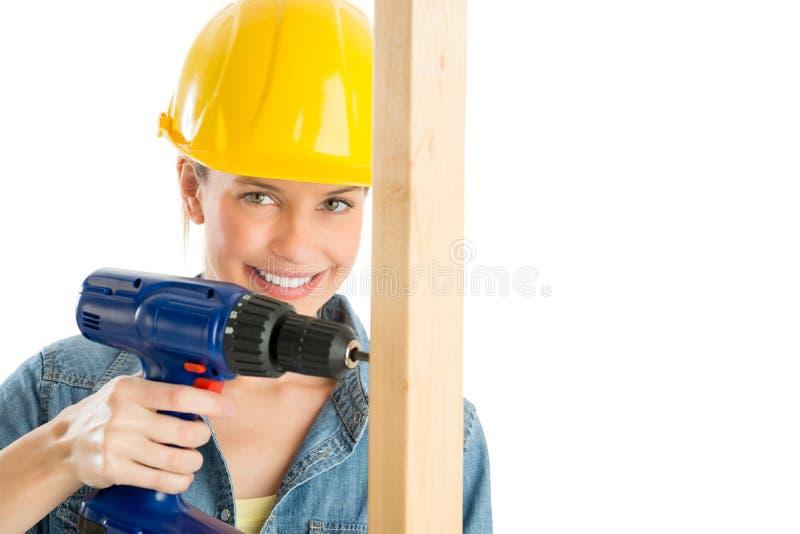 Θηλυκός εργάτης οικοδομών που τρυπά την ξύλινη σανίδα με τρυπάνι στοκ εικόνες
