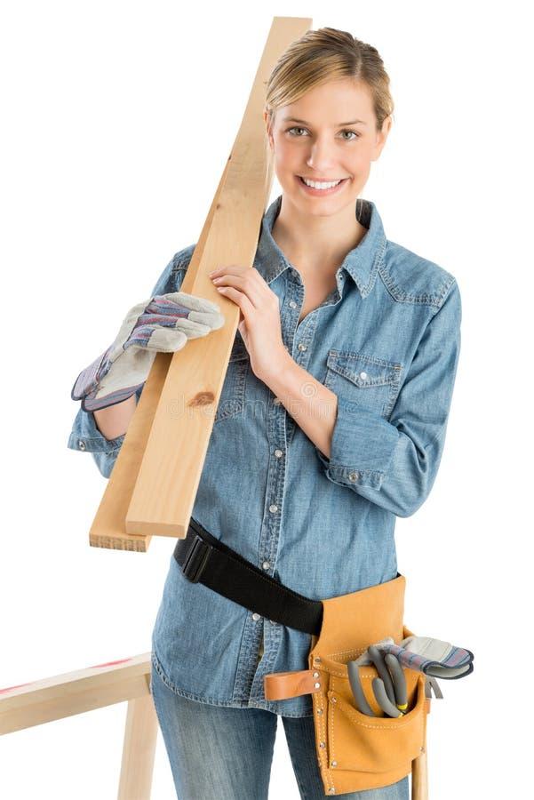 Θηλυκός εργάτης οικοδομών που φέρνει την ξύλινη σανίδα στον ώμο στοκ εικόνα με δικαίωμα ελεύθερης χρήσης