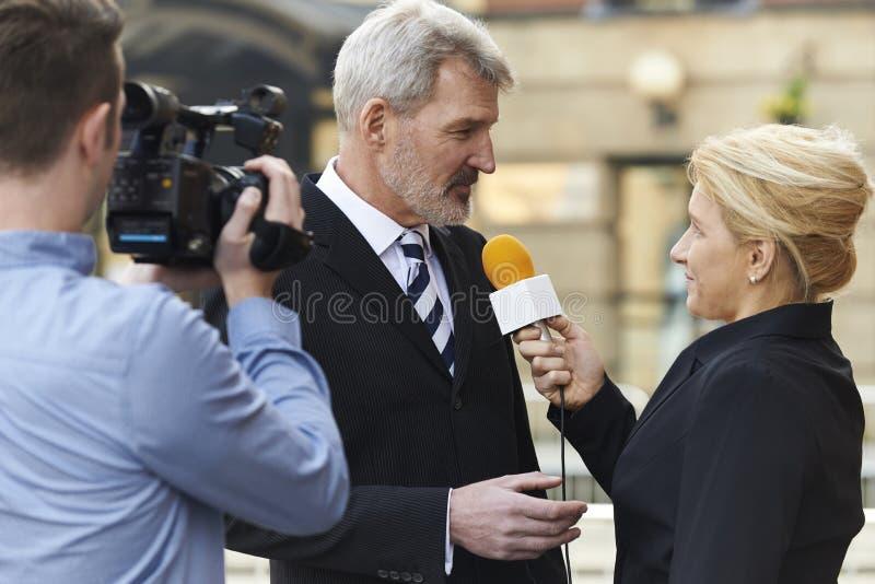 Θηλυκός δημοσιογράφος με το μικρόφωνο που παίρνει συνέντευξη από τον επιχειρηματία στοκ εικόνα