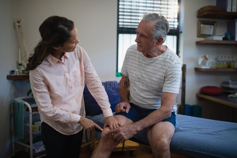 Θηλυκός θεράπων που δείχνει στο γόνατο μιλώντας με τον ανώτερο αρσενικό ασθενή στοκ εικόνες
