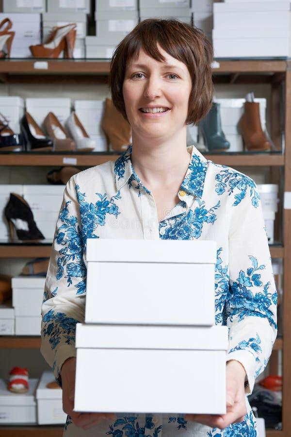 Θηλυκός ιδιοκτήτης των φέρνοντας κιβωτίων καταστημάτων παπουτσιών στοκ φωτογραφία με δικαίωμα ελεύθερης χρήσης