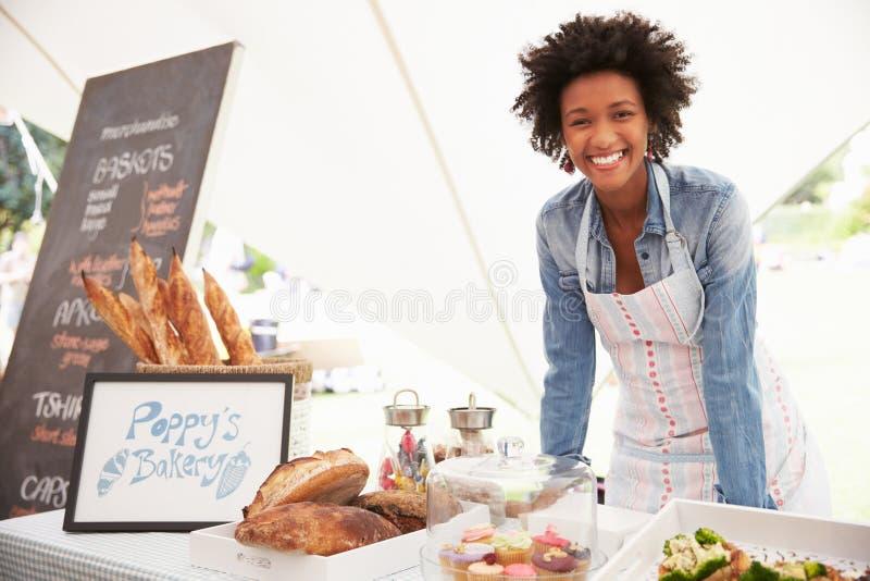 Θηλυκός κάτοχος στάβλων αρτοποιείων στη φρέσκια αγορά τροφίμων αγροτών στοκ φωτογραφίες