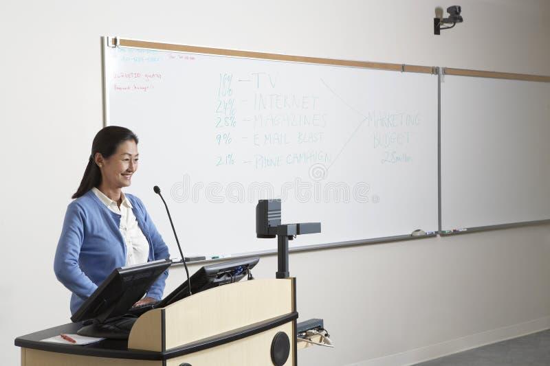 Θηλυκός καθηγητής Standing στην εξέδρα στοκ φωτογραφίες