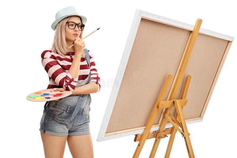 Θηλυκός καλλιτέχνης που εξετάζει μια ζωγραφική στοκ εικόνες