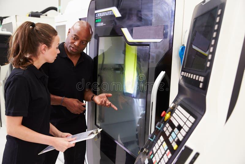 Θηλυκός μαθητευόμενος που συνεργάζεται με το μηχανικό CNC στα μηχανήματα στοκ εικόνες