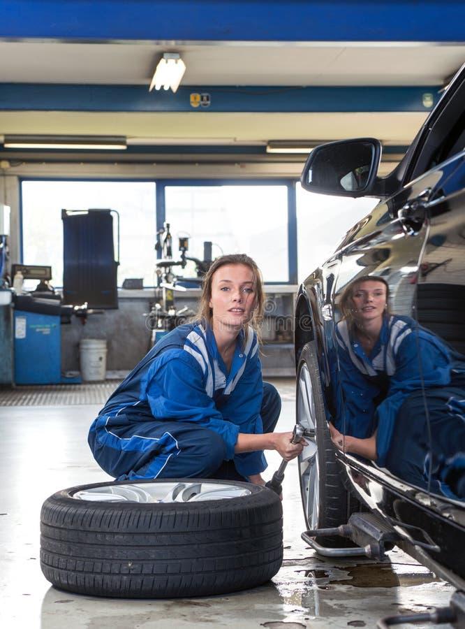 Θηλυκός μηχανικός που αλλάζει ένα ελαστικό αυτοκινήτου στοκ εικόνα με δικαίωμα ελεύθερης χρήσης