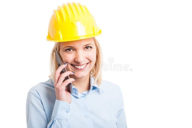 Θηλυκός μηχανικός που φορά το κράνος που μιλά στο τηλέφωνο στοκ φωτογραφία