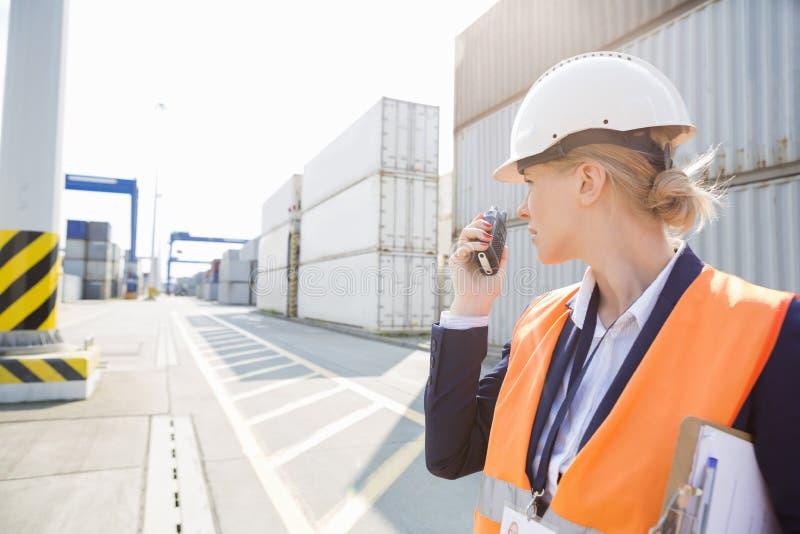 Θηλυκός μηχανικός που χρησιμοποιεί walkie-talkie στη ναυτιλία του ναυπηγείου στοκ εικόνα