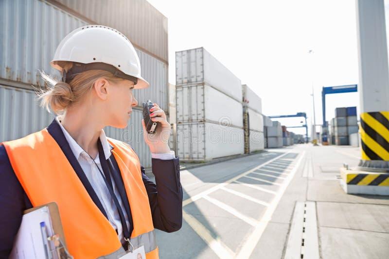 Θηλυκός μηχανικός που χρησιμοποιεί walkie-talkie στη ναυτιλία του ναυπηγείου στοκ εικόνα με δικαίωμα ελεύθερης χρήσης