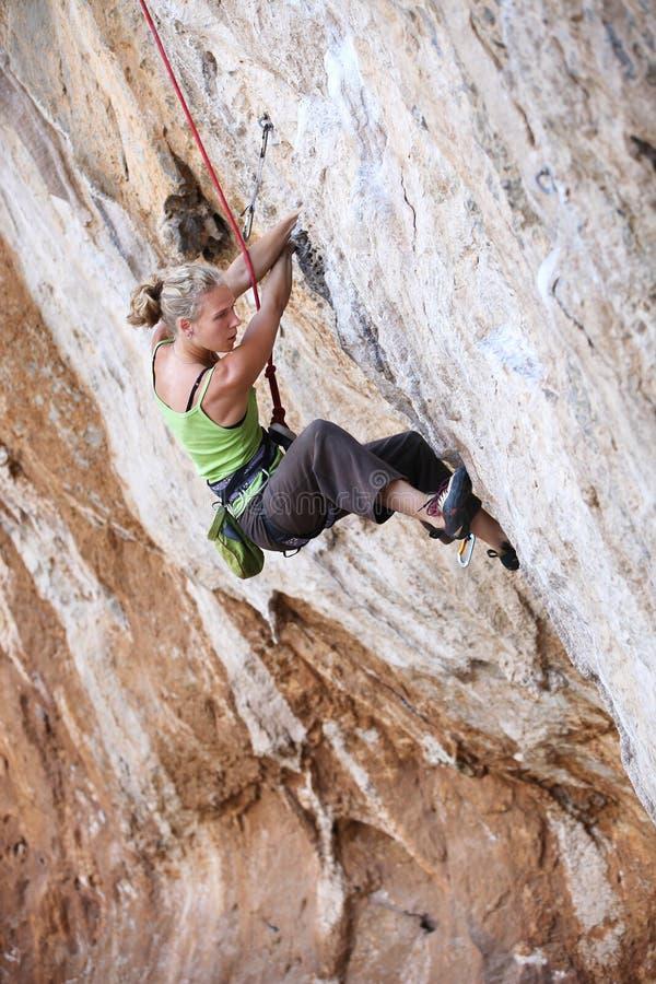 Θηλυκός ορειβάτης βράχου σε ένα πρόσωπο απότομων βράχων στοκ εικόνες