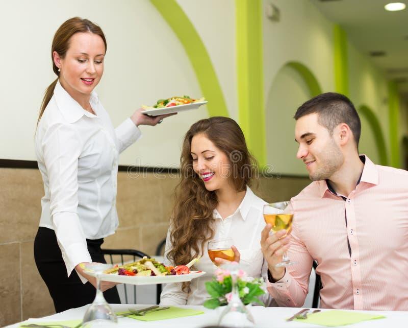 Θηλυκός πίνακας φιλοξενουμένων σερβιτόρων εξυπηρετώντας στοκ φωτογραφία