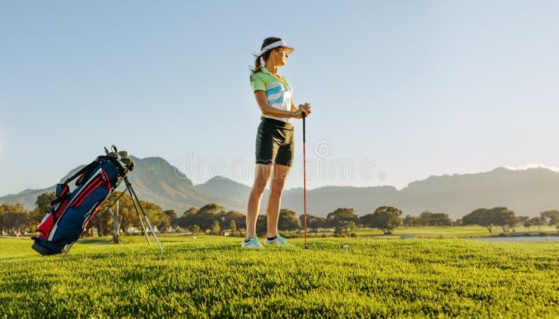 Θηλυκός παίκτης γκολφ στο γήπεδο του γκολφ που περιμένει να τοποθετήσει στο σημείο αφετηρίας μακριά στοκ εικόνες με δικαίωμα ελεύθερης χρήσης