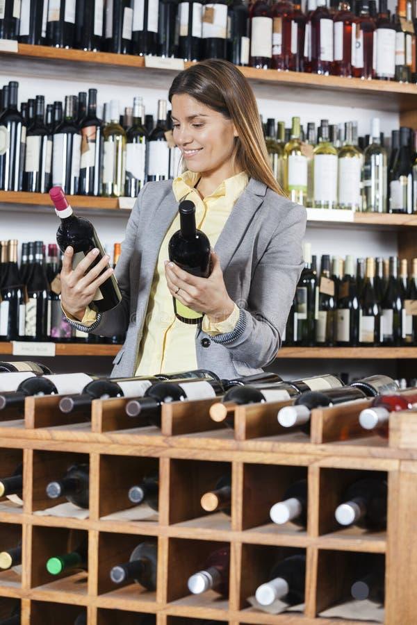 Θηλυκός πελάτης που εξετάζει τα μπουκάλια κρασιού στην οινοποιία στοκ φωτογραφίες με δικαίωμα ελεύθερης χρήσης