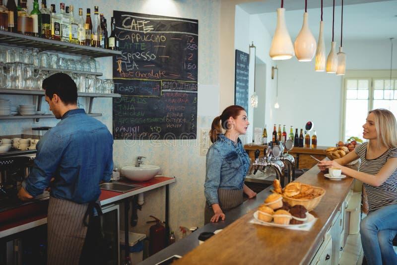Θηλυκός πελάτης που μιλά με το barista στον καφέ στοκ φωτογραφία