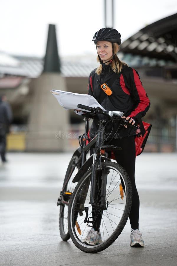 Θηλυκός ποδηλάτης με την τσάντα και τη συσκευασία αγγελιαφόρων επάνω στοκ εικόνα