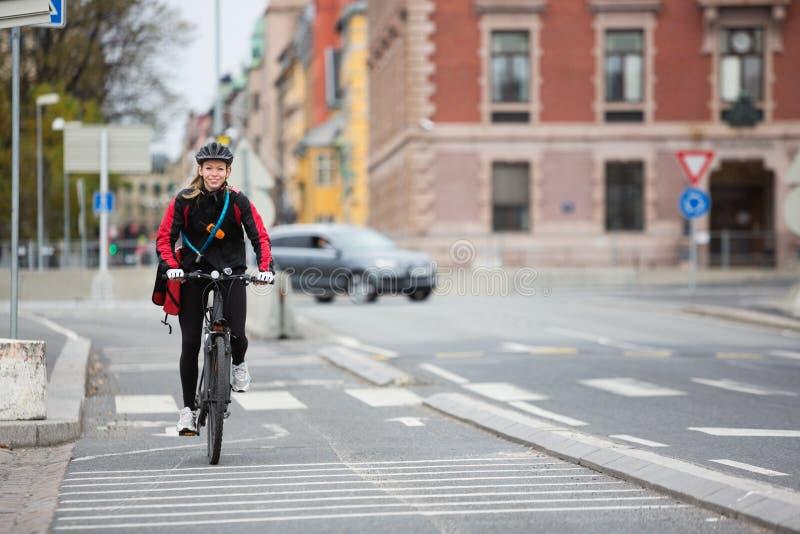 Θηλυκός ποδηλάτης με την τσάντα παράδοσης αγγελιαφόρων στην οδό στοκ εικόνες