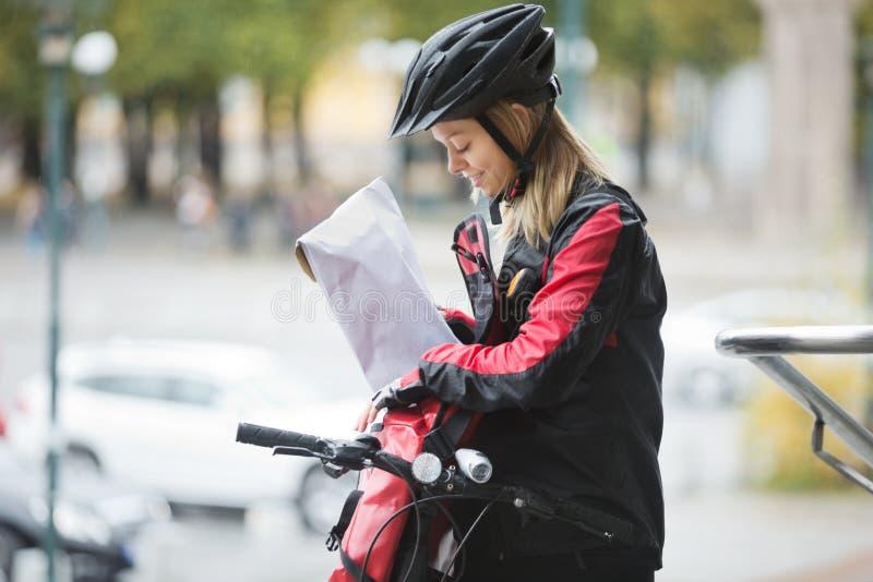 Θηλυκός ποδηλάτης που βάζει τη συσκευασία στην τσάντα αγγελιαφόρων στοκ εικόνες