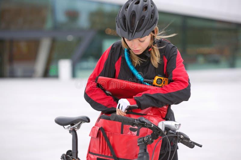 Θηλυκός ποδηλάτης που κοιτάζει μέσω της παράδοσης αγγελιαφόρων στοκ εικόνες με δικαίωμα ελεύθερης χρήσης