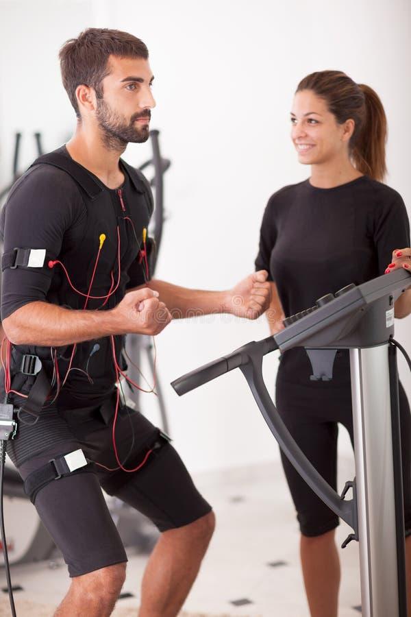 Θηλυκός προπονητής που δίνει στο άτομο EMS το ηλεκτρο μυϊκό exerci υποκίνησης στοκ εικόνες