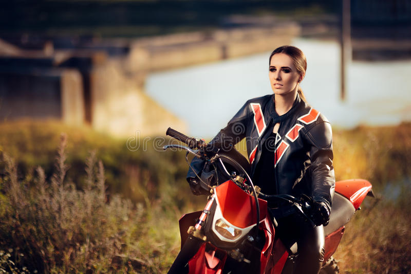 Θηλυκός δρομέας μοτοκρός δίπλα στη μοτοσικλέτα της στοκ εικόνες