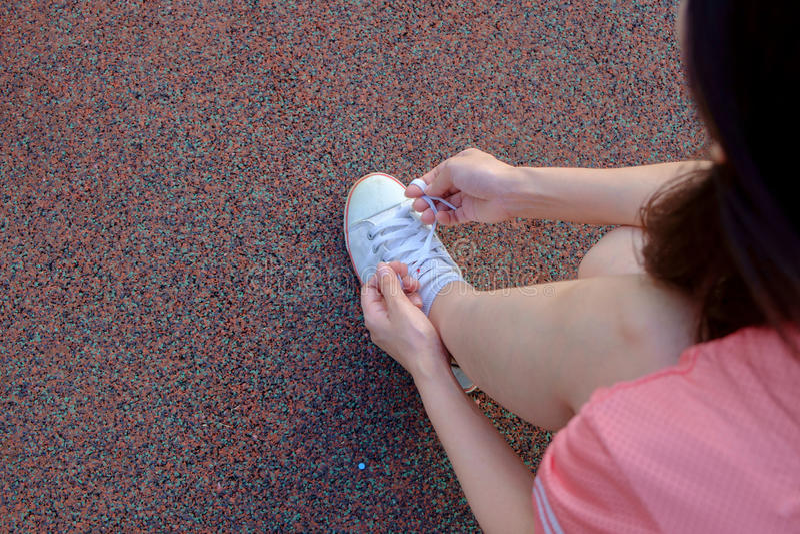 Θηλυκός δρομέας που δένει το αθλητικό παπούτσι της στοκ φωτογραφία