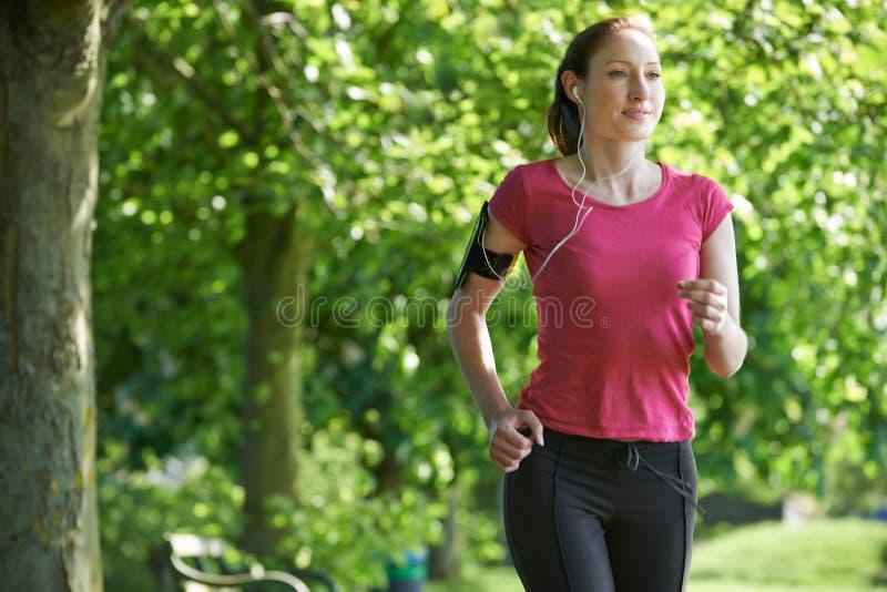 Θηλυκός δρομέας στο πάρκο με τη φορετή τεχνολογία στοκ εικόνες