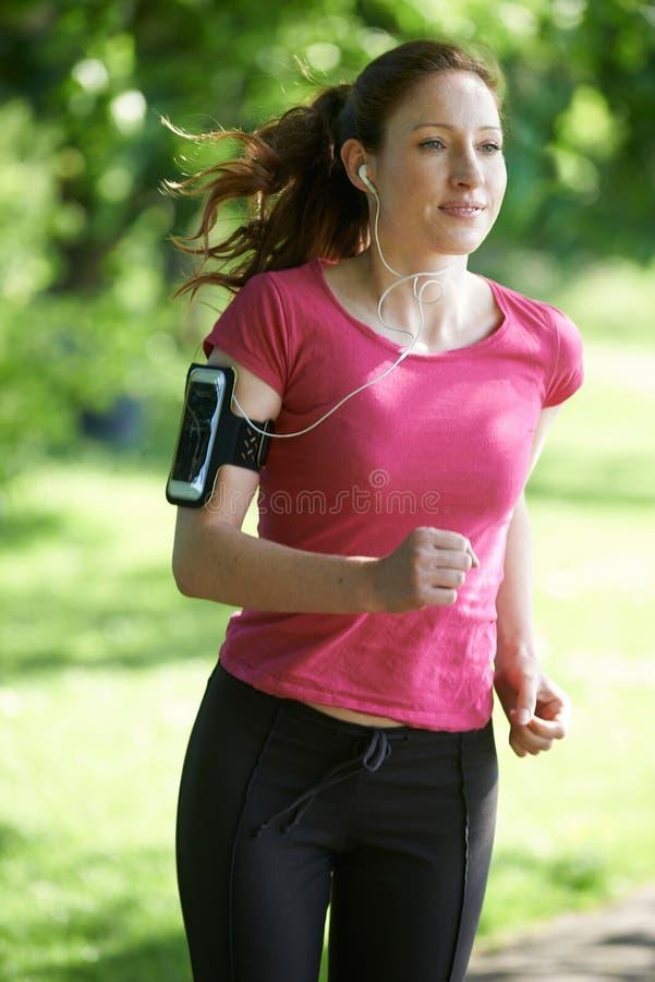 Θηλυκός δρομέας στο πάρκο με τη φορετή τεχνολογία στοκ φωτογραφίες με δικαίωμα ελεύθερης χρήσης