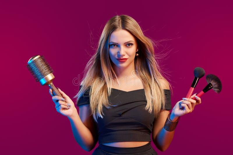 Θηλυκός στιλίστας που στέκεται με το hairdresser& x27 εξαρτήματα και makeup βούρτσες του s στοκ εικόνες