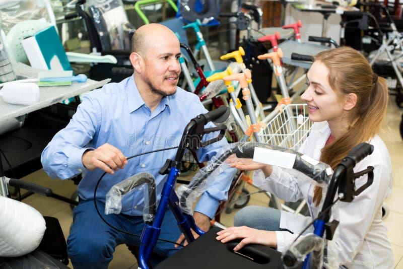 Θηλυκός σύμβουλος που προσφέρει την αναπηρική καρέκλα στον ώριμο πελάτη στοκ εικόνες με δικαίωμα ελεύθερης χρήσης