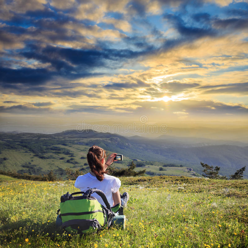 Θηλυκός ταξιδιώτης με το σακίδιο πλάτης που κάνει τη φωτογραφία του βουνού lanscape στοκ φωτογραφία με δικαίωμα ελεύθερης χρήσης