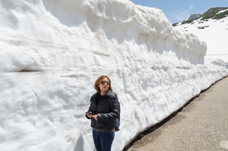 Θηλυκός τοίχος ταξιδιωτών και χιονιού στην αλπική διαδρομή tateyama ορών της Ιαπωνίας kurobe στοκ φωτογραφία