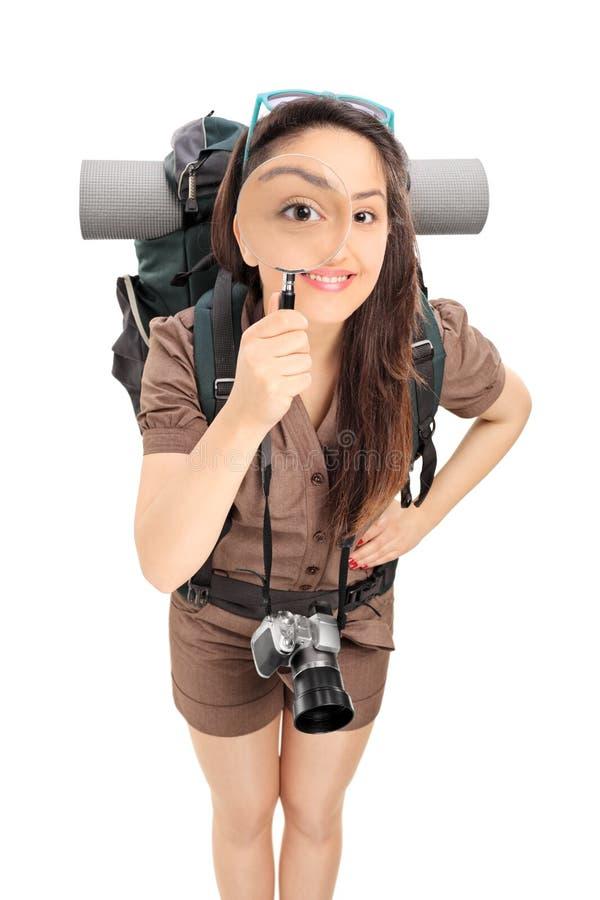 Θηλυκός τουρίστας που κοιτάζει μέσω μιας ενίσχυσης - γυαλί στοκ εικόνα