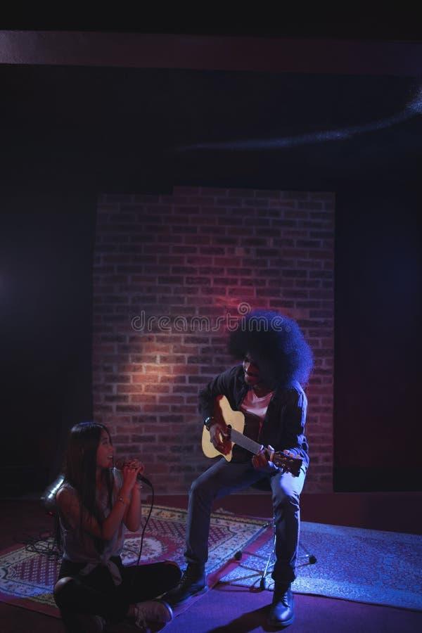 Θηλυκός τραγουδιστής με την άσκηση κιθαριστών στο νυχτερινό κέντρο διασκέδασης στοκ φωτογραφία με δικαίωμα ελεύθερης χρήσης