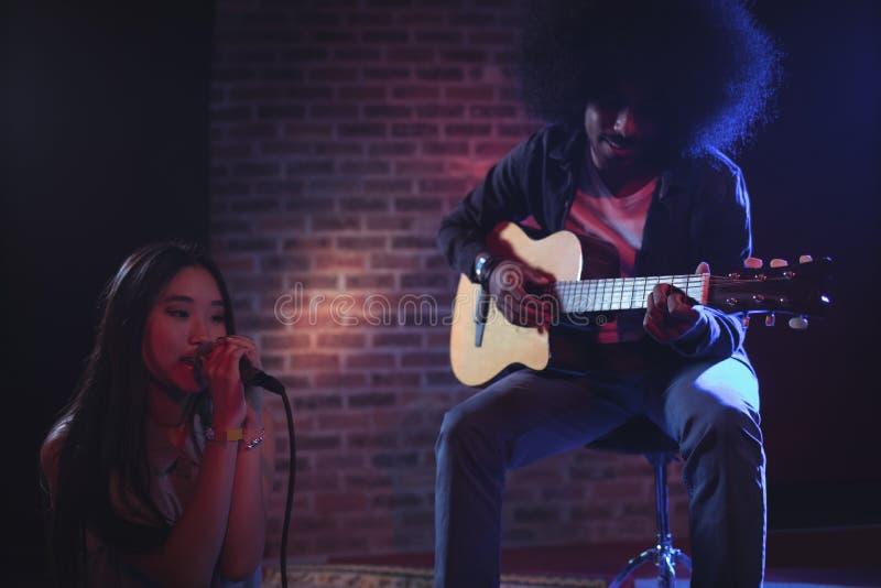 Θηλυκός τραγουδιστής με το αρσενικό νυχτερινό κέντρο διασκέδασης κιθαριστών στοκ εικόνες