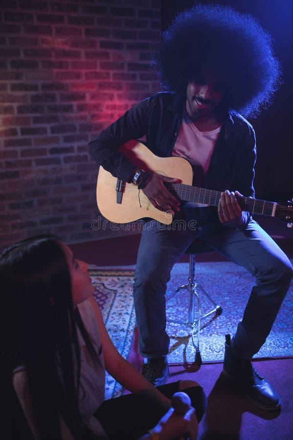 Θηλυκός τραγουδιστής που επικοινωνεί με τον αρσενικό κιθαρίστα στο νυχτερινό κέντρο διασκέδασης στοκ φωτογραφία