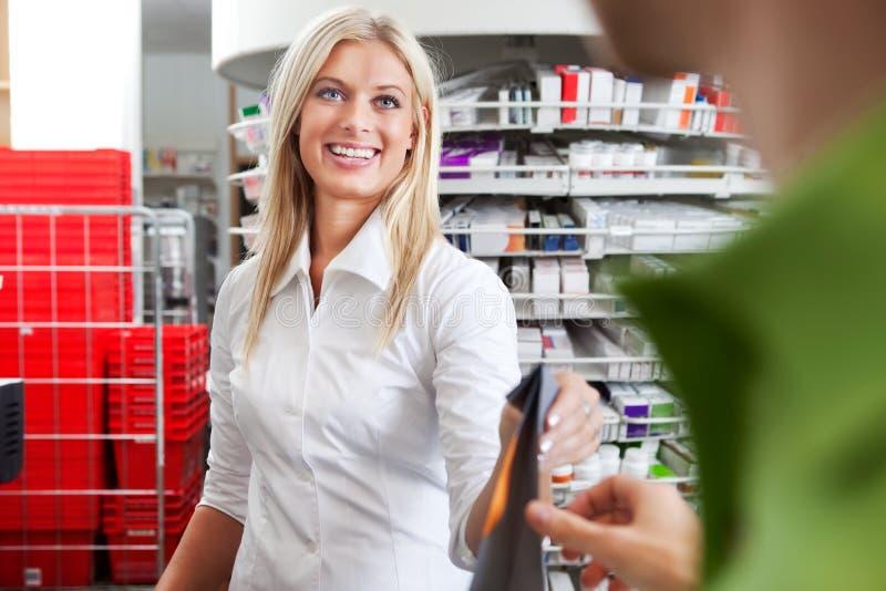Θηλυκός φαρμακοποιός με έναν πελάτη στο φαρμακείο στοκ εικόνα με δικαίωμα ελεύθερης χρήσης