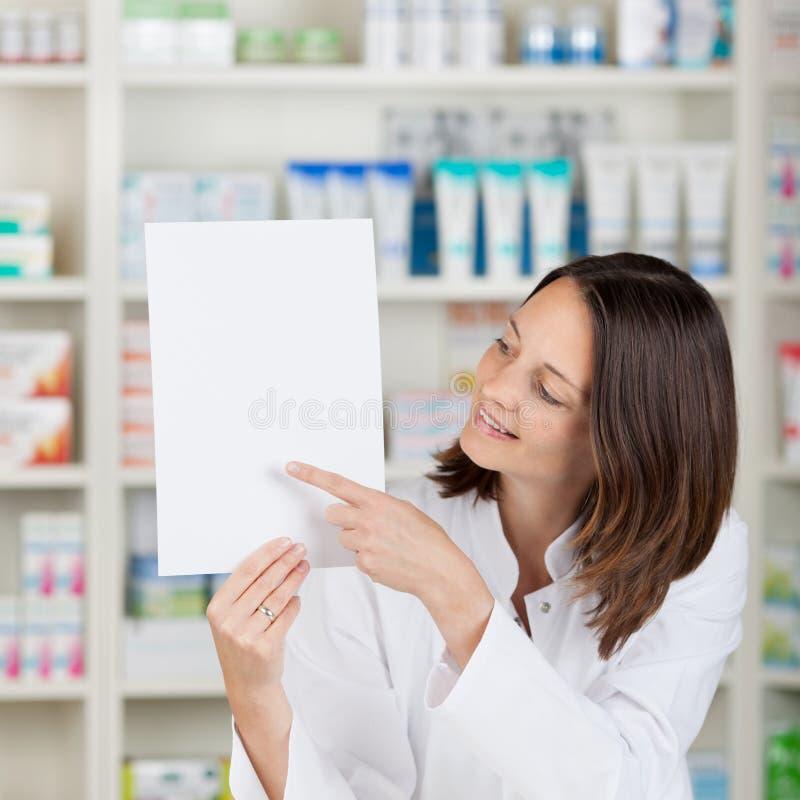 Θηλυκός φαρμακοποιός που δείχνει σε κενό χαρτί στο φαρμακείο στοκ φωτογραφία